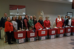A group of school officials and Enrichment staff with tote containers filled with hats and gloves.