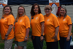 Enrichment employees stand together at Habitat For Humanity home being built.