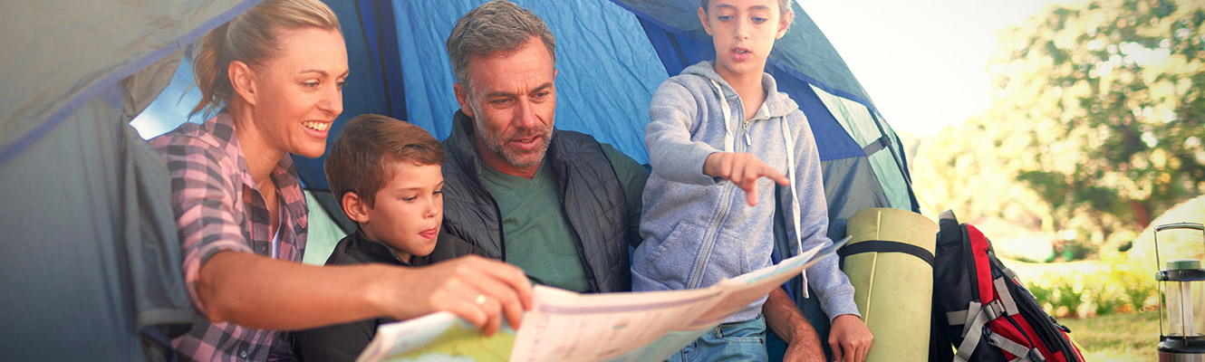 Family sitting outside their tent looking at a map while camping.