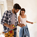 Young couple measuring in new home construction.