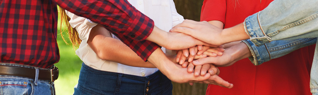 A group of individuals with their hands overlaying each other.