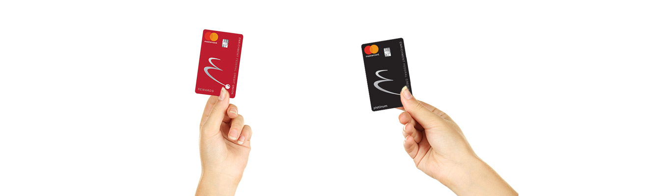 Two hands holding two different Enrichment credit cards.