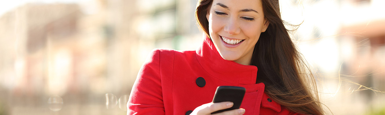 Young woman in red jacket holding phone with city background.