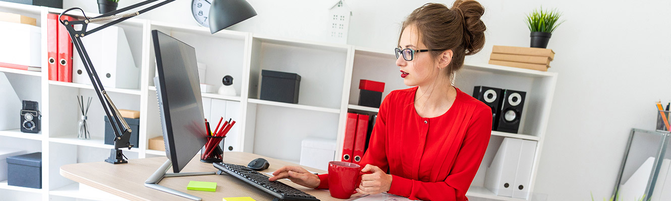 Woman sitting at a desk working on the computer.